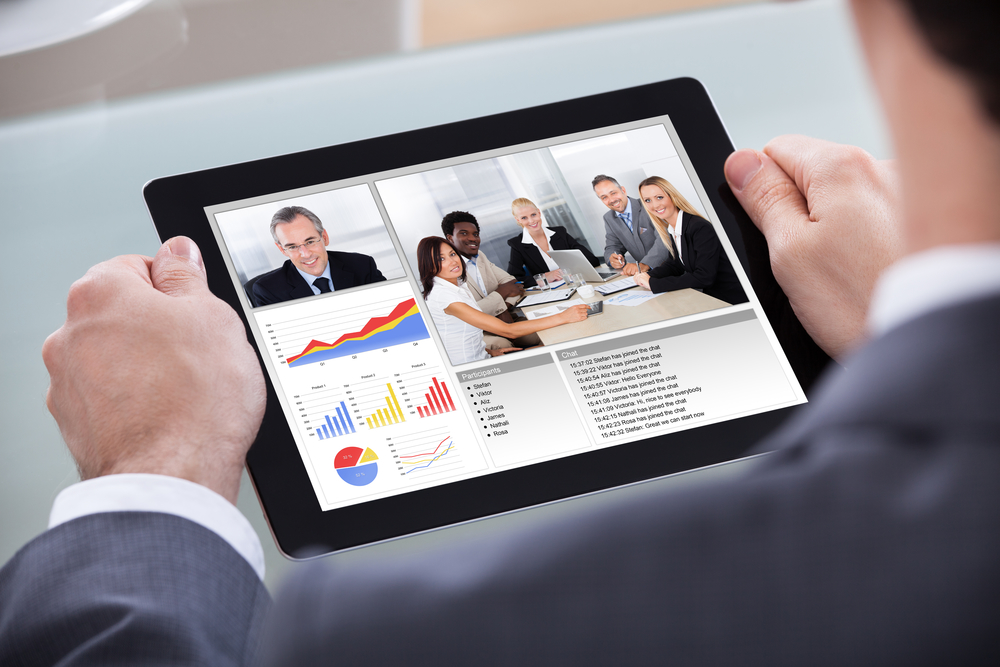 Close-up Of Businessman Video Conferencing With Co-worker About Progress Chart