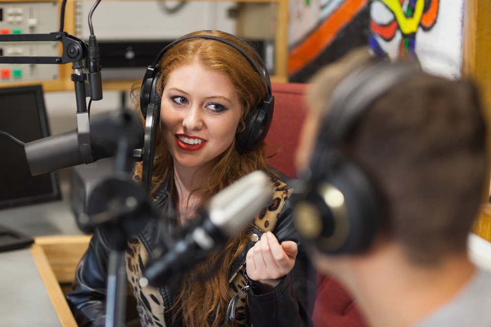 Attractive happy radio host interviewing a guest in studio at college
